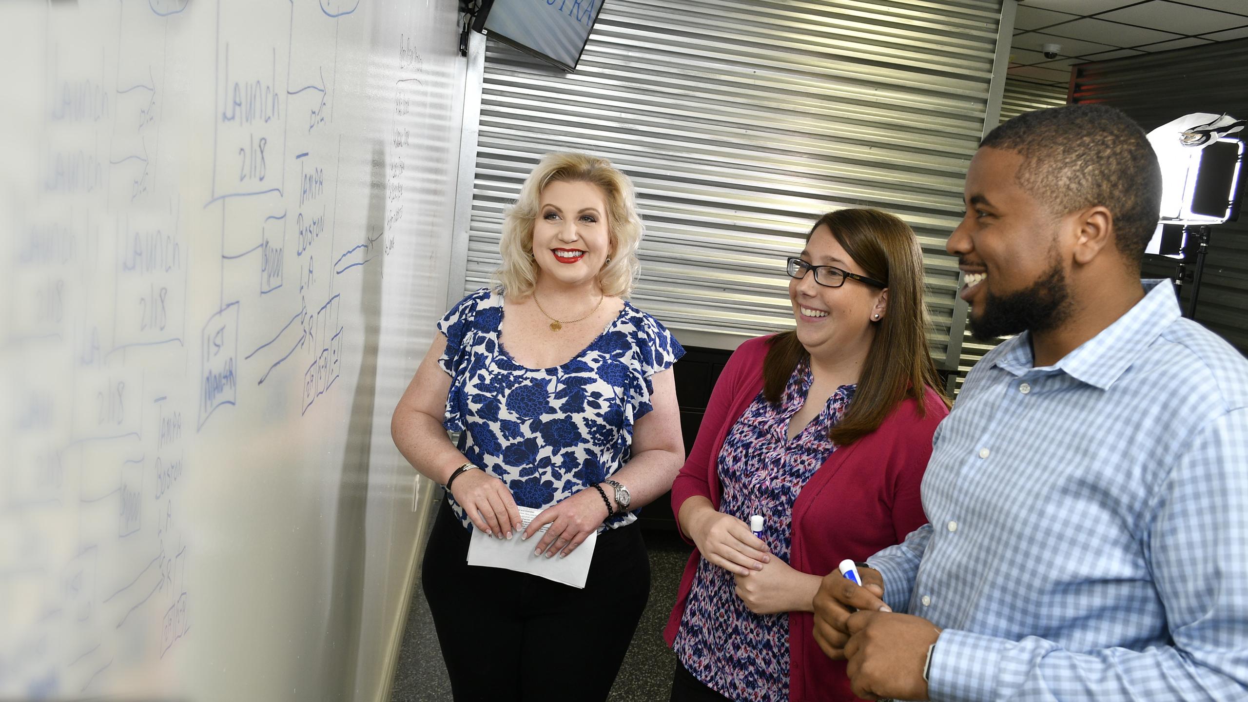 Team members strategizing at the whiteboard.